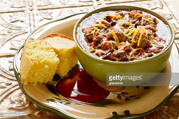 bowl of chili with shredded cheese and corn bread - chili stock photos and pictures