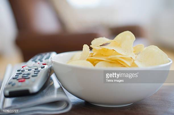 Bowl of chips beside remote control