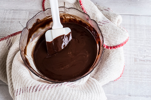 A bowl of chocolate brownie ingredients being stirred by a spatula. - gettyimageskorea