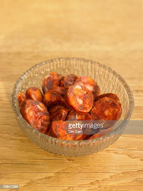 Bowl of chorizo on wooden table, close-up