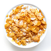 Bowl of cornflakes in milk isolated on white from above.