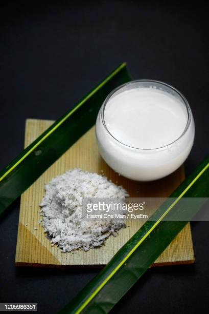 bowl of cream of coconut milk on black background - frische stockfoto's en -beelden