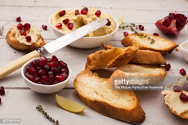 A bowl of creamy hummus with olive oil pomegranate and herbs