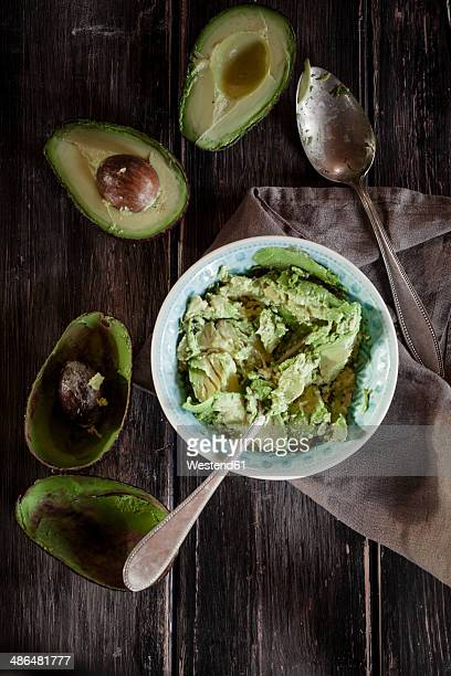 Bowl of crushed avocado, kitchen towel, spoon and sliced and hollowed halfs of two avocados on wooden table