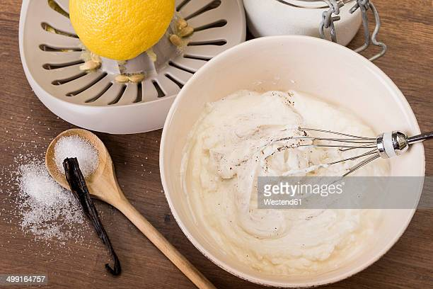 Bowl of curd and other ingredients for creme on wooden table