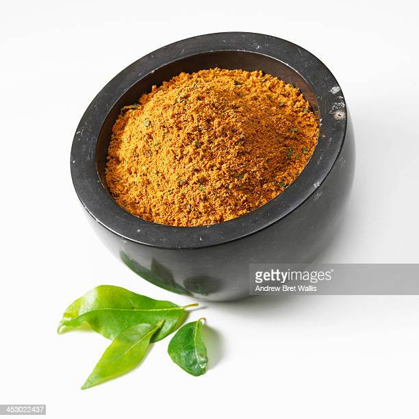 Bowl of curry powder and fresh curry leaves