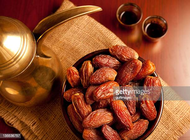 Bowl of dates and tea set on top of a native place mat
