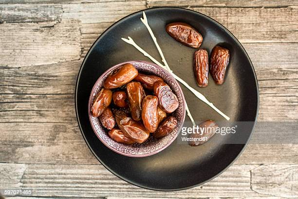 Bowl of dates, skewers and plate on wood