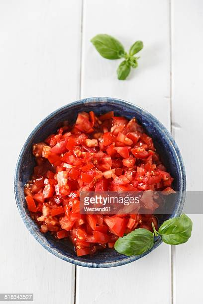 Bowl of diced tomatoes and basil leaves on white wood, elevated view