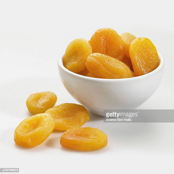 bowl of dried apricots against white - apricot stock pictures, royalty-free photos & images