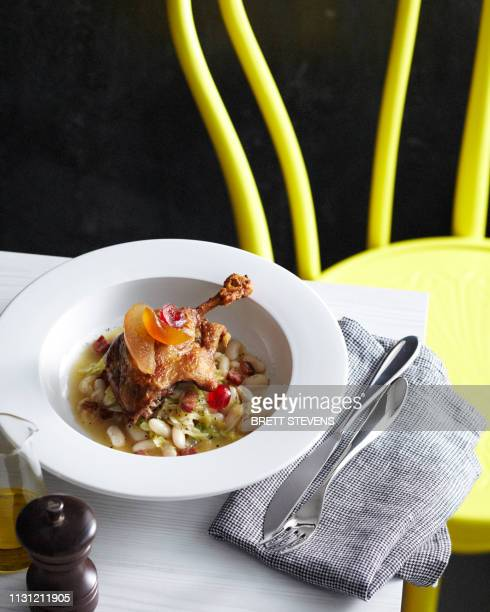 Bowl of duck leg confit with candied fruit garnish served on beans