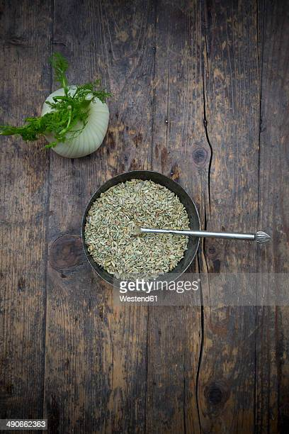 Bowl of fennel seeds and fennel corm (Foeniculum vulgare) on wooden table