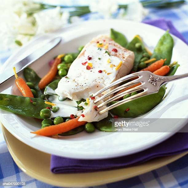 Bowl of fish and spring vegetables, close-up