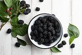 Bowl of fresh blackberries on stone background