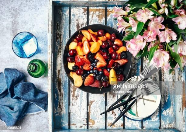 bowl of fresh fruit on a blue, wooden tray - 果物の盛り合わせ ストックフォトと画像