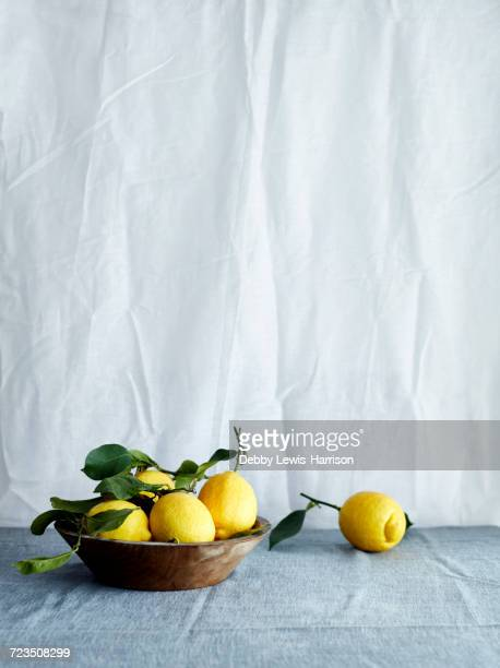Bowl of fresh lemons in bowl on tablecloth