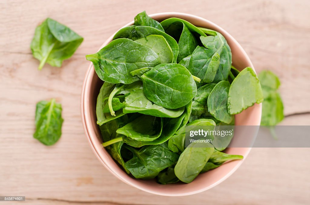 Bowl of fresh spinach leaves on wood : Stock Photo
