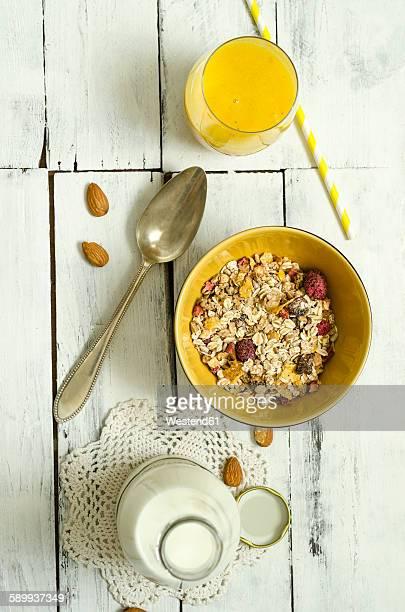 Bowl of fruit muesli, glass of mango smoothie, spoon and bottle of milk