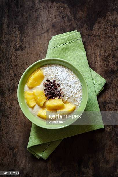 Bowl of fruit smoothie garnished with pineapple slices, coconut flakes and chocolate shaving