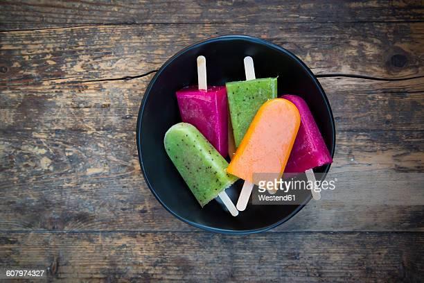 Bowl of fruit smoothie ice lollies on dark wood