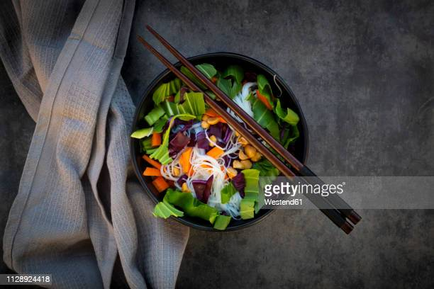 Bowl of glass noodle salad with vegetables and peanuts