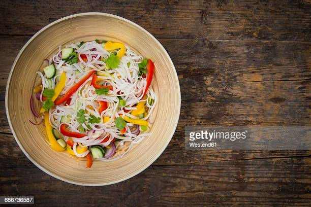 Bowl of glass noodle salad with vegetables on dark wood