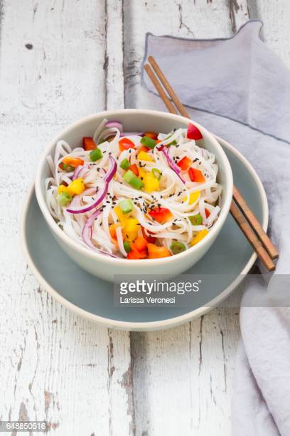 Bowl of glass noodle salad with vegetables on wood