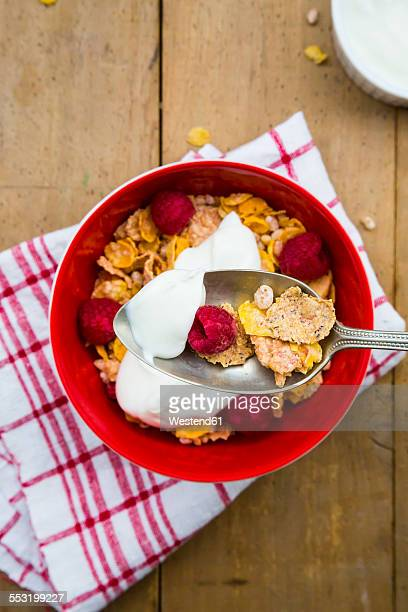 Bowl of glutenfree cereals with natural yoghurt and raspberries