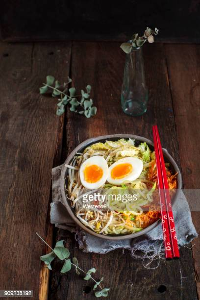 Bowl of glutenfree Udon noodle soup with carrots, Chinese cabbage, zoodles, mungo beans sprouts and boiled egg