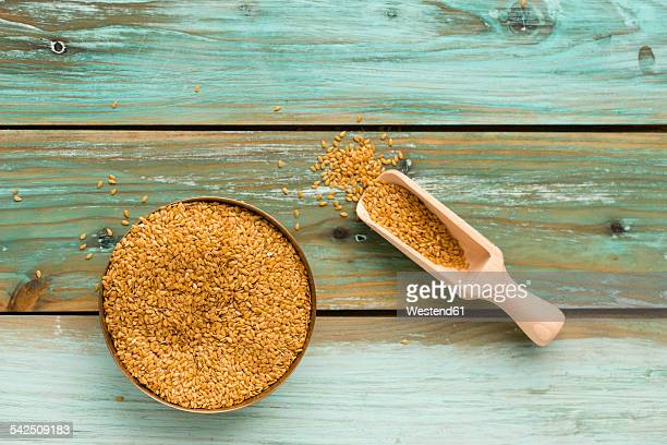 Bowl of golden linseed and shovel on green wood