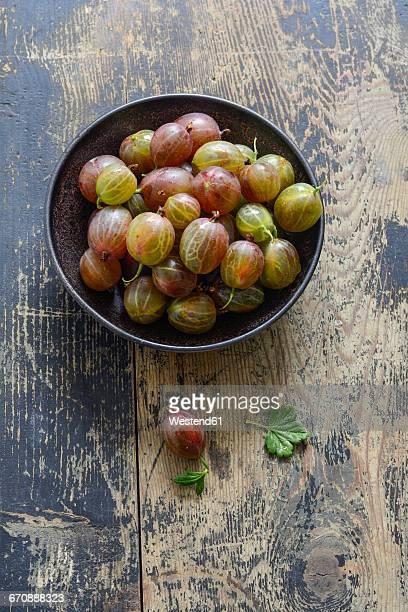 Bowl of gooseberries on wood
