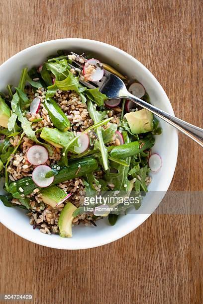 Bowl of grains & arugula salad & zucchini
