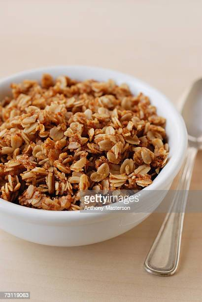 bowl of granola beside spoon, elevated view, studio - anthony-masterson stock pictures, royalty-free photos & images