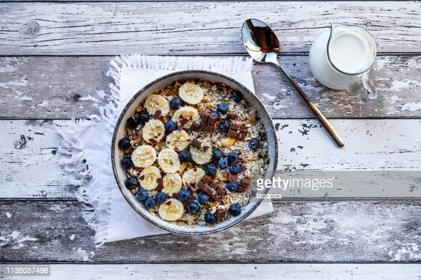 bowl of granola with banana slices, blueberries and chocolate - granola stock pictures, royalty-free photos & images