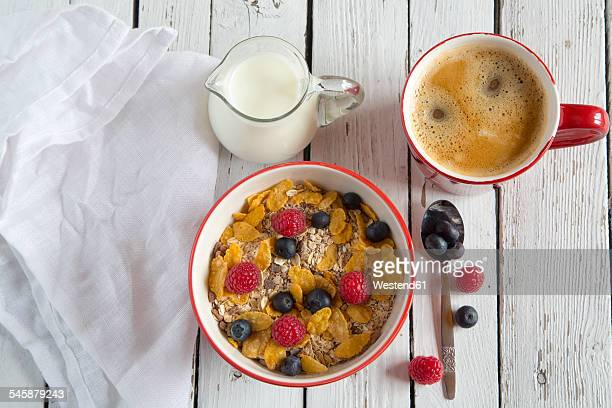 Bowl of granola with fresh fruits, cup of coffee and milk jug on white wood