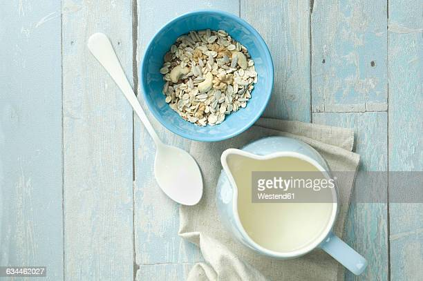 Bowl of granola with walnuts, cashew nuts, sunflower seed and a milk jug
