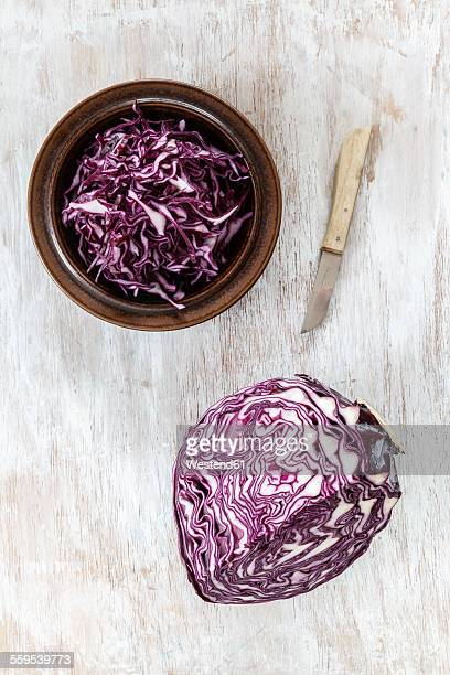 Bowl of grated red cabbage, kitchen knife and piece of red cabbage