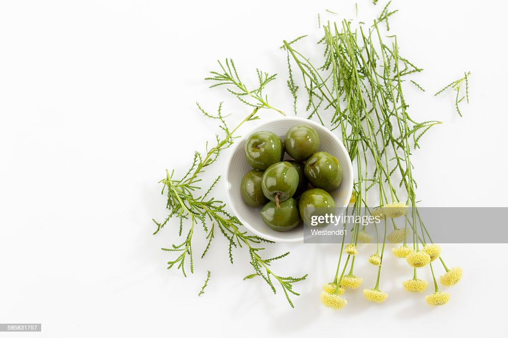 Bowl of green olives and green santolina : Stock Photo