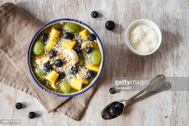 Bowl of green smoothie and fruits sprinkled with coconut flakes