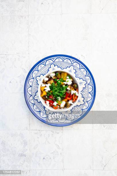 bowl of grilled eggplant and bell peppers with goat cheese and parsley - larissa veronesi stock-fotos und bilder