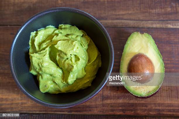 bowl of guacamole and half of an avocado on wood - guacamole stock photos and pictures
