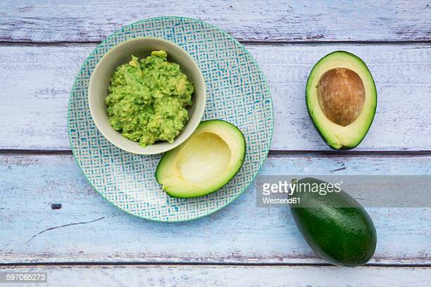 Bowl of Guacamole and whole and sliced avocados on light blue wood