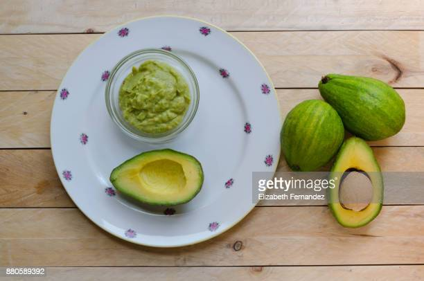 Bowl of Guacamole and whole and sliced avocados on wooden background