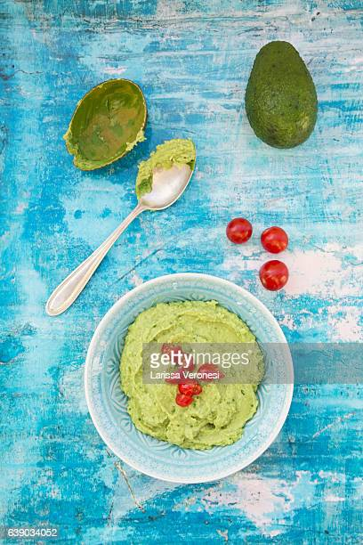 Bowl of guacamole, Avocado and Tomatoes on blue surface