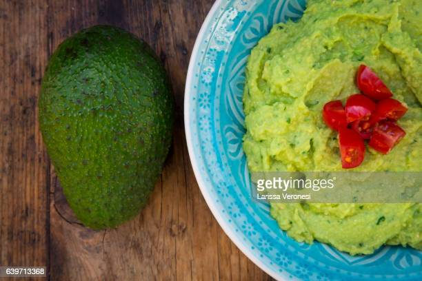 Bowl of guacamole, Avocado and Tomatoes on dark wood