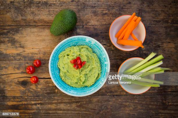 Bowl of guacamole, Avocado, celery, carrots and Tomatoes on dark wood