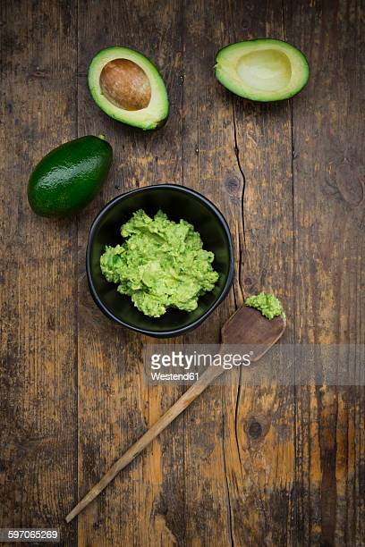 Bowl of Guacamole, cooking spoon and whole and sliced avocados on dark wood