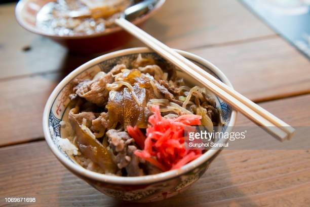a bowl of gyudon with a pair of chopsticks - takayama city stock pictures, royalty-free photos & images