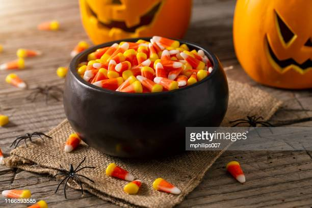 bowl of halloween candy corns and jack o' lantern - happy halloween stock photos and pictures