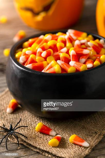 bowl of halloween candy corns and jack o' lantern - candy corn stock photos and pictures